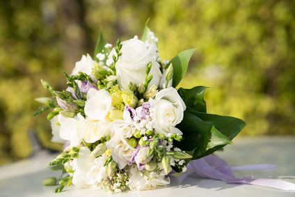 Wedding bouquet with white roses on green nature background